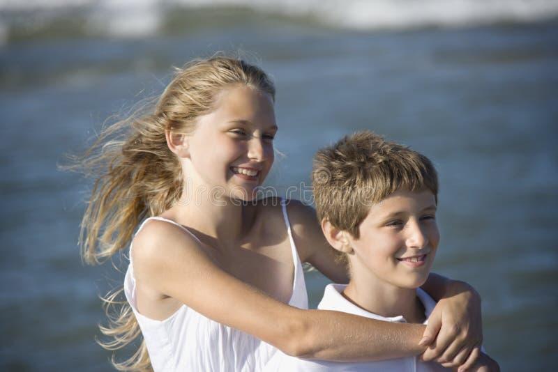 Schwester, die ihren Bruder umarmt lizenzfreie stockfotografie
