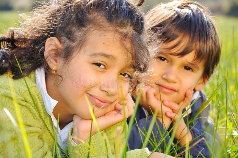 Schwester und Bruder auf grüner Wiese lizenzfreies stockfoto