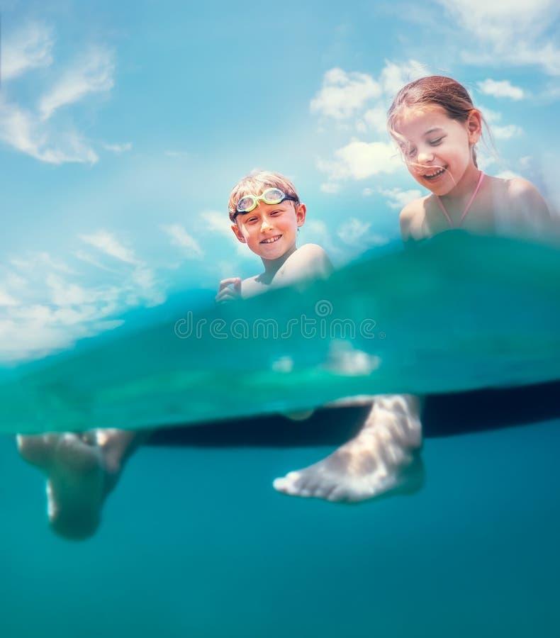 Schwester und Bruder, die auf aufblasbarer Matratze sitzt und das Meerwasser, nett lachend wenn Schwimmen im Meer genie?t unvorsi lizenzfreie stockbilder