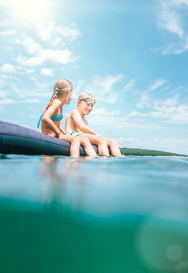 Schwester und Bruder, die auf aufblasbarer Matratze sitzt und das Meerwasser, nett lachend wenn Schwimmen im Meer genie?t unvorsi stockbilder