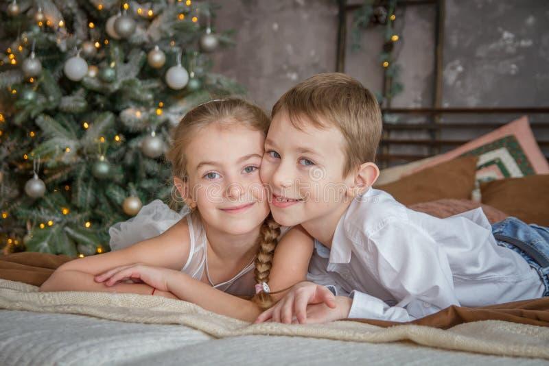 Schwester und Bruder, die auf Sofa unter Weihnachtsbaum liegen lizenzfreie stockbilder