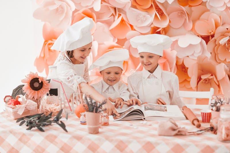 Schwester und zwei kleine K?che fangen an, Abendessen vorzubereiten stockfotos