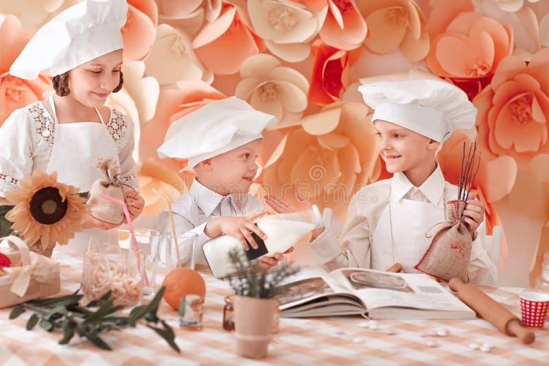 Schwester und zwei kleine K?che fangen an, Abendessen vorzubereiten stockbilder