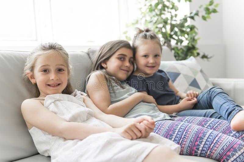 Schwestermädchen der besten Freunde auf dem Sofa, das Spaß hat lizenzfreies stockfoto