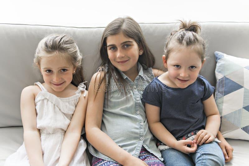 Schwestermädchen der besten Freunde auf dem Sofa, das Spaß hat stockfoto