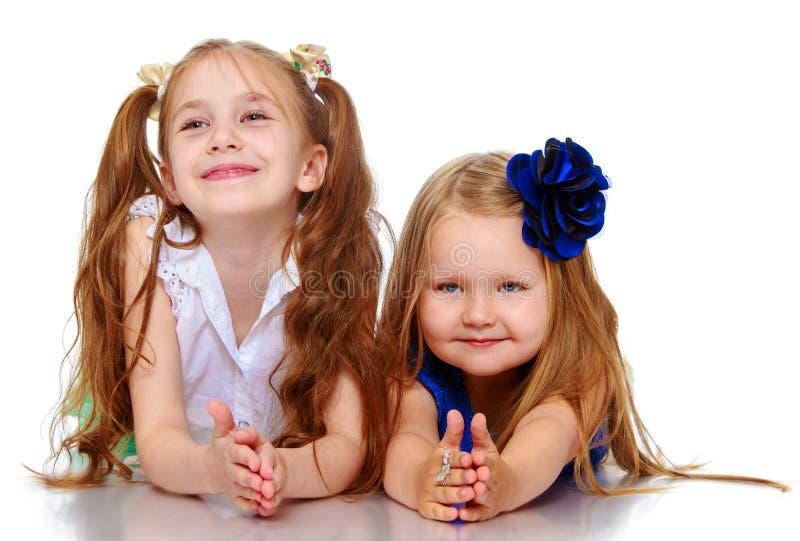 Schwestern, die auf dem Boden liegen lizenzfreie stockfotografie