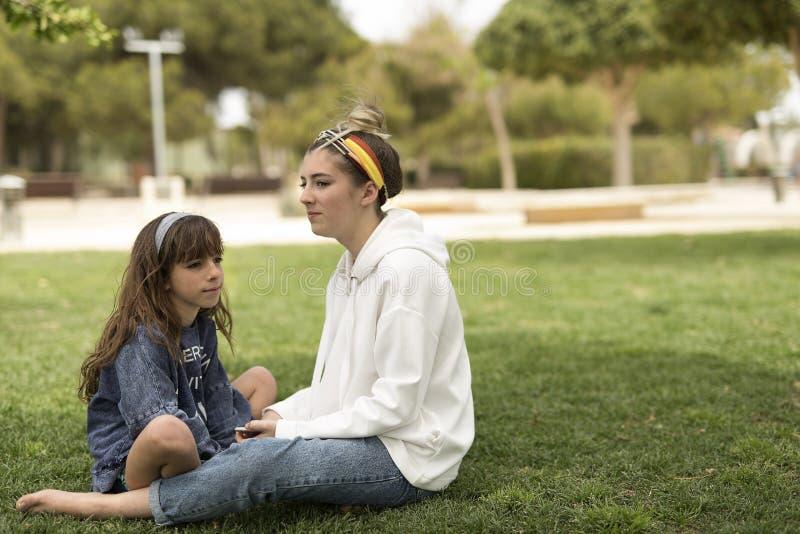Schwestern, die auf dem Gras mit ernsten Gesichtern sitzen lizenzfreies stockbild