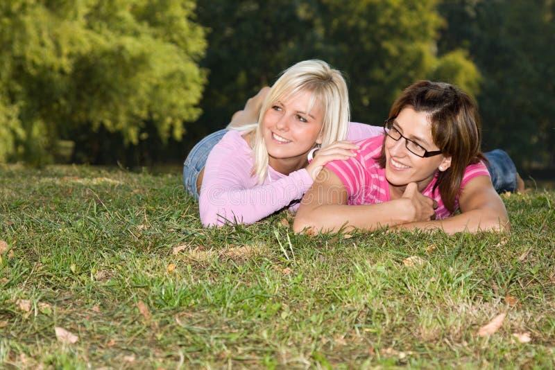 Schwestern, die in das Gras legen lizenzfreies stockbild