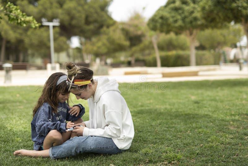 Schwestern, die einen Handy in einem Park betrachten lizenzfreies stockfoto