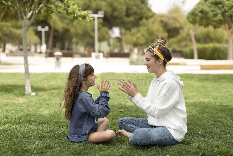 Schwestern, die glücklich in einem Park spielen lizenzfreie stockfotos