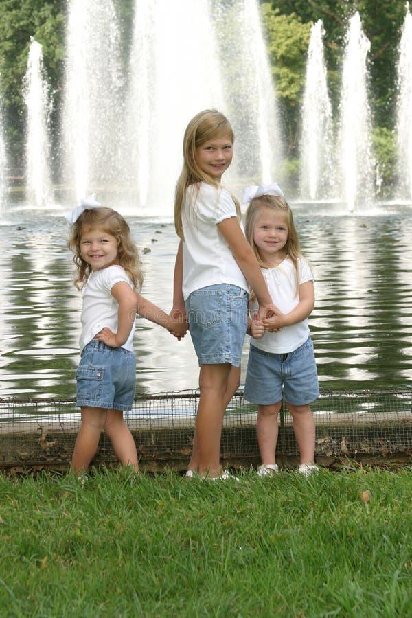Schwestern, die Hände anhalten stockfoto