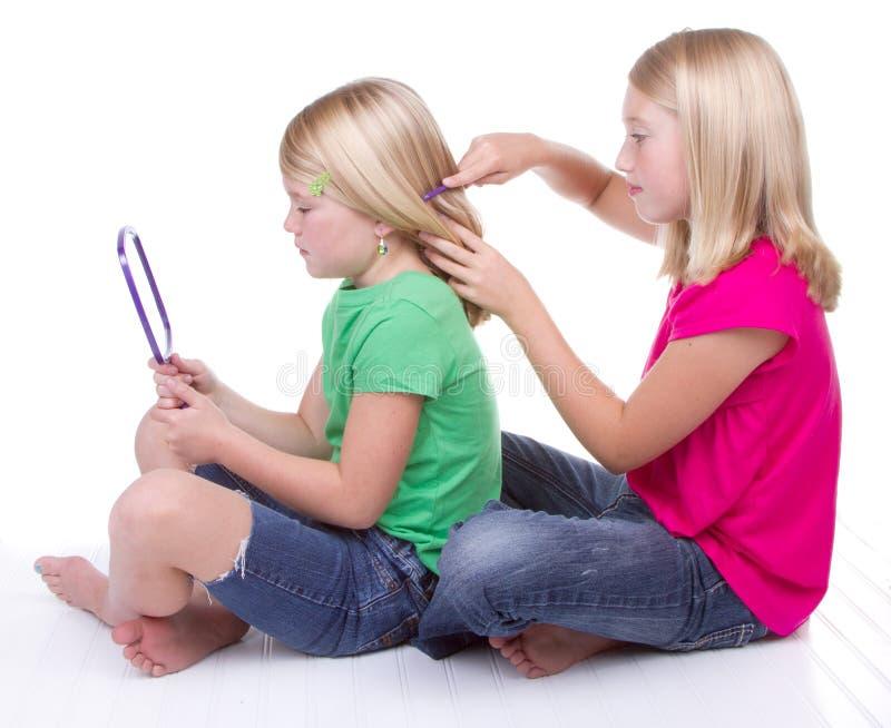 Schwestern, die Haar kämmen lizenzfreie stockbilder