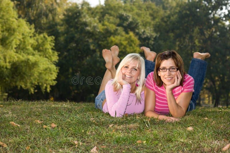 Schwestern, die im Park liegen stockfotos