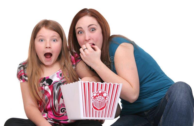 Schwestern, die Popcorn essen lizenzfreie stockfotografie