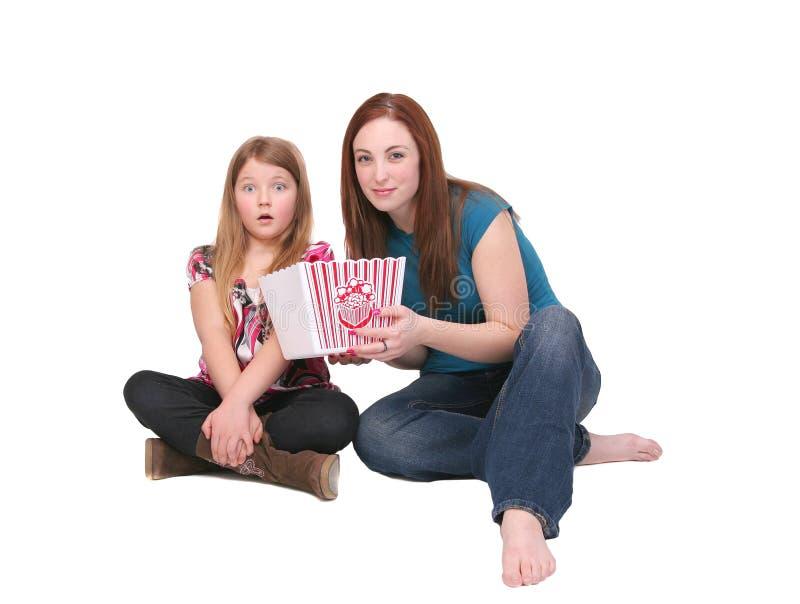 Schwestern, die Popcorn essen stockbilder