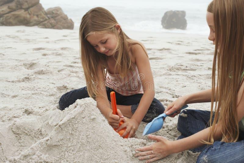 Schwestern, die Sandburg am Strand machen stockfotos