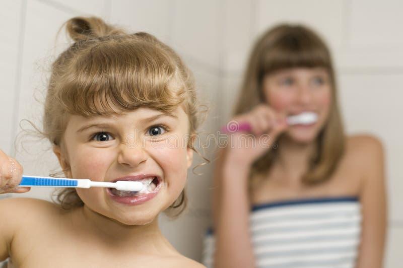 Schwestern, die Zähne putzen lizenzfreie stockbilder