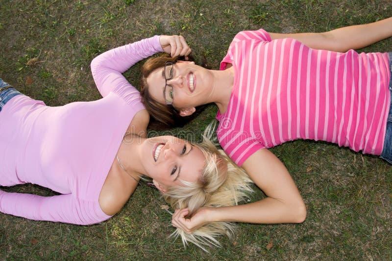 Schwestern entspannen sich im Gras stockbilder