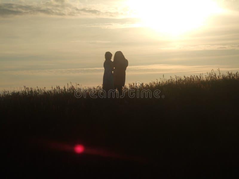 Schwestern im Sonnenuntergang lizenzfreie stockfotografie