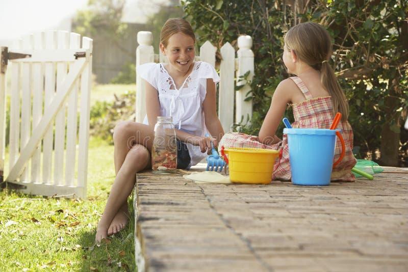 Schwestern mit den Strand-Spielwaren, die im Yard sitzen stockfotografie
