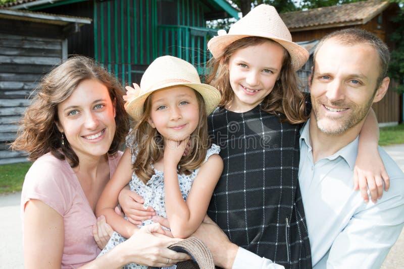 Schwestern mit Hut und Mutter bringen Ferien der Familie draußen hervor stockfotografie