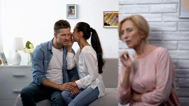 Schwiegermutter, heimlich zuhörende Ehefrau, die auf dem Ohr des Ehemanns geheim flüstert stockfotos