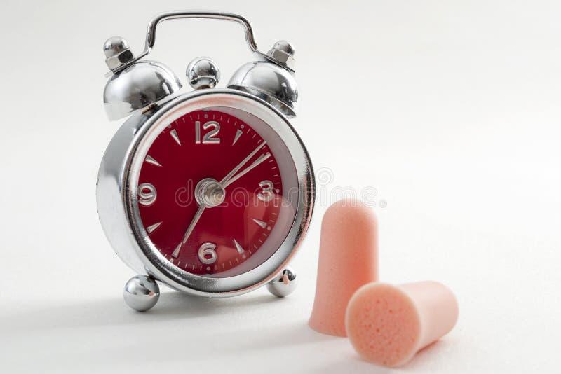 Schwierigkeit, die einschlafen, Schlafenprobleme und Schlaflosigkeit wegen der lauten Geräusche mit einem Wecker und ein Paar Ohr stockfoto