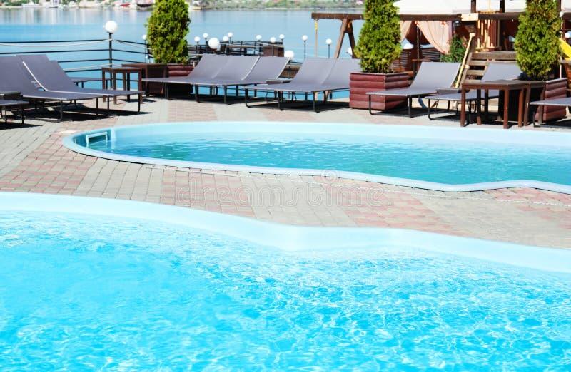 Schwimmbäder mit sauberem blauem Wasser und Klubsesseln stockbild