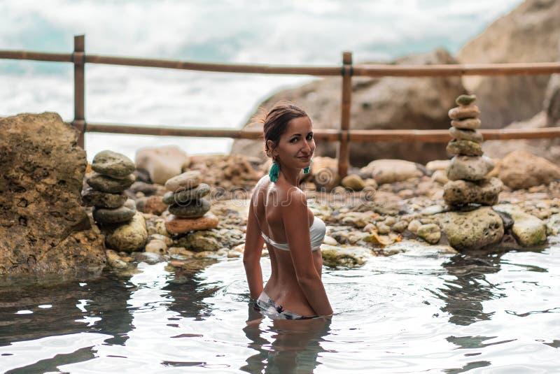 Schwimmen der jungen Frau in einem natürlichen Pool auf dem Hintergrund des Ozeans lizenzfreies stockbild