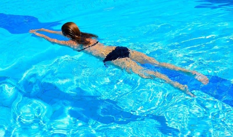 Schwimmen der jungen Frau im Pool lizenzfreie stockfotografie