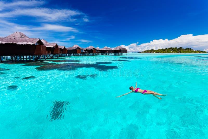Schwimmen der jungen Frau von der Hütte in der tropischen Lagune lizenzfreie stockfotografie