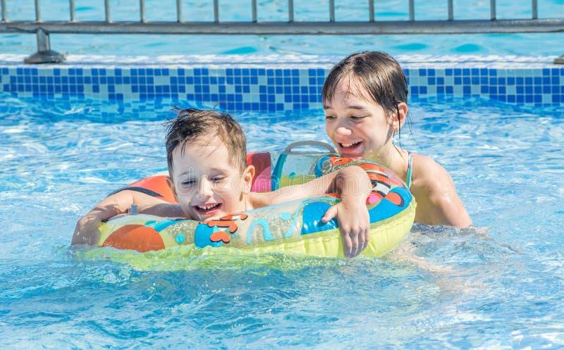 Schwimmen der ?lteren Schwester und des j?ngeren Bruders im im Freien Pool der Kinder lizenzfreie stockfotos