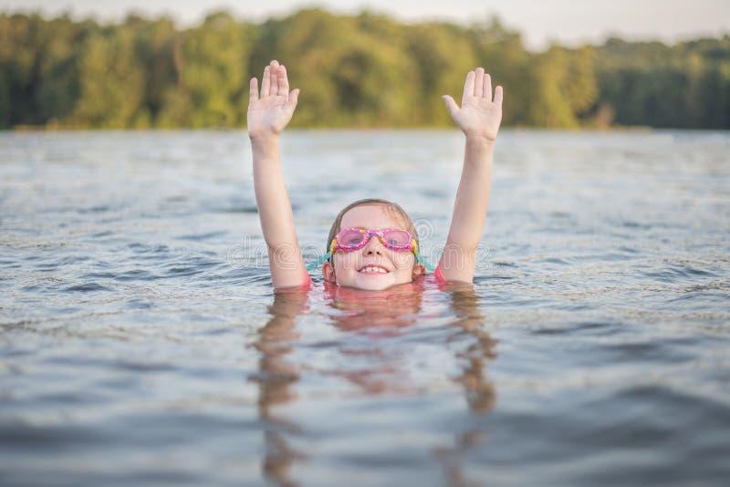 Schwimmen des jungen Mädchens in der Seeholding überreicht ihren Kopf stockfotos