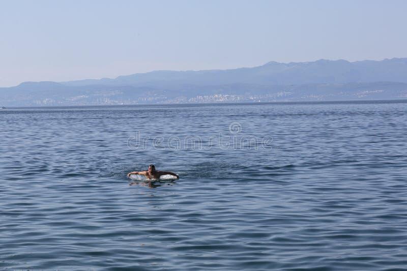 Schwimmen des jungen Mannes im adriatischen Meer lizenzfreies stockbild