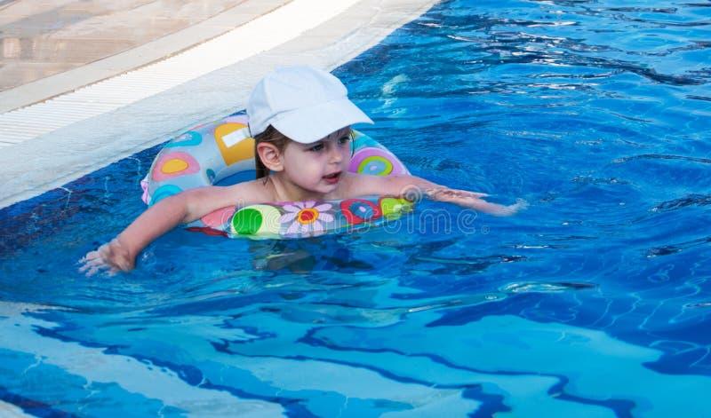 Schwimmen des kleinen Mädchens in einem Pool stockfoto