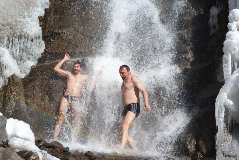 Schwimmen im Winterwasserfall lizenzfreies stockbild
