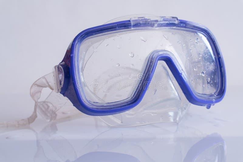 Schwimmende Maske des blauen Silikons auf weißer Tabelle mit Reflexion stockfoto