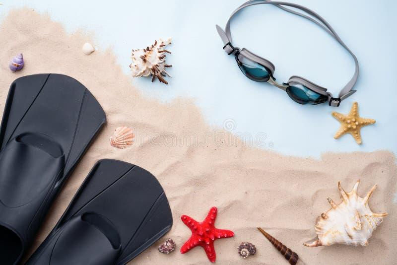 Schwimmende Schutzbrillen und Flipper auf dem Sand mit Oberteilen und Starfishes stockfotografie