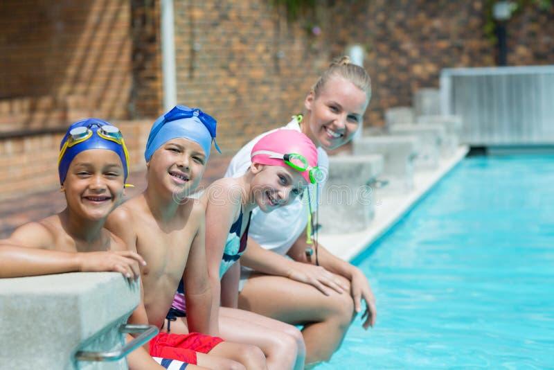 Schwimmenlehrer mit den Studenten, die am Poolside sitzen lizenzfreie stockfotografie