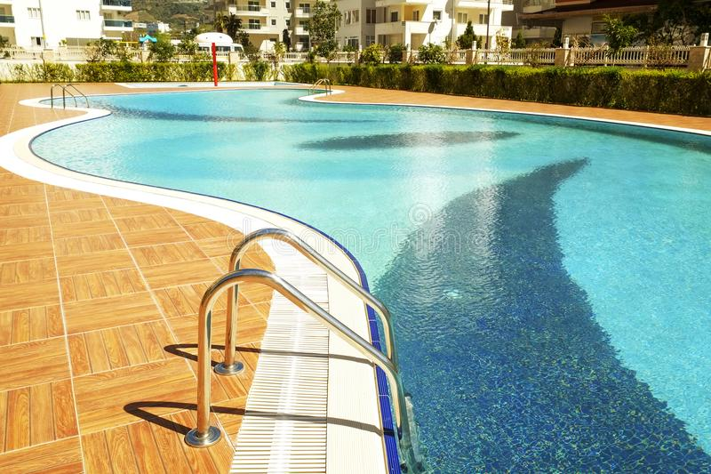 Schwimmenpoolbereich des neuen Luxuswohnkomplexes mit Fliesen, Chromtreppengriffen und Abflüssen Sonniger schöner Tag stockfoto