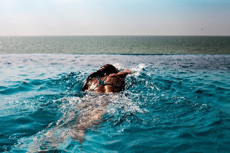 Schwimmenschleichenart der jungen Frau in einem Pool mit Seeansicht und blauem Himmel stockbild