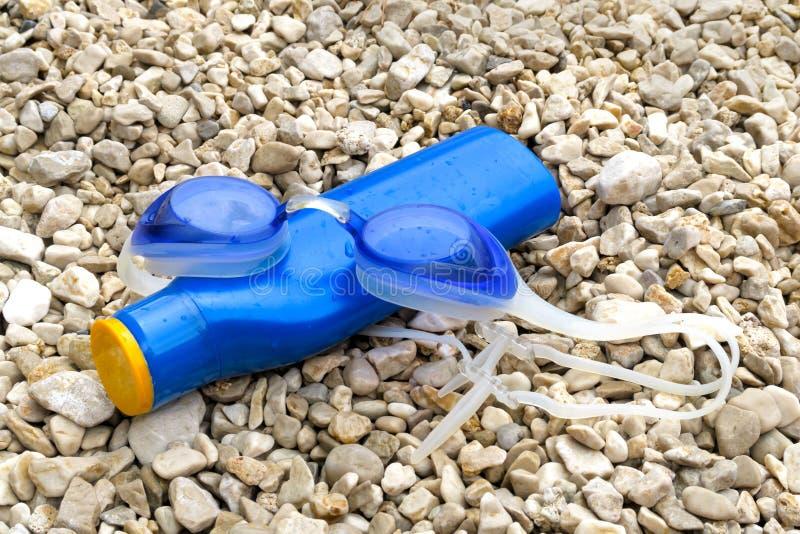 Schwimmenschutzbrillen und -Sonnenschutzmittel auf Pebble Beach stockbild