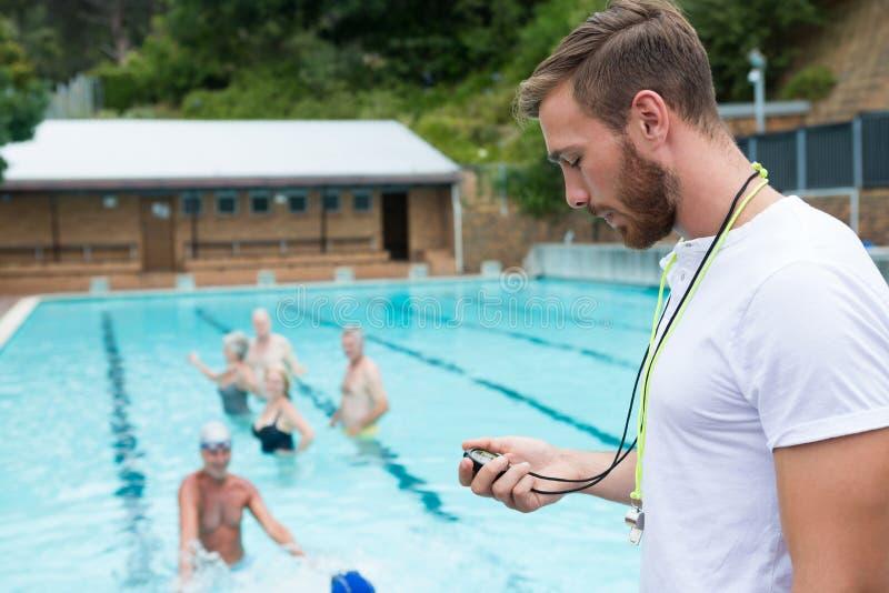 Schwimmentrainer, der Stoppuhr nahe Poolside betrachtet stockfoto