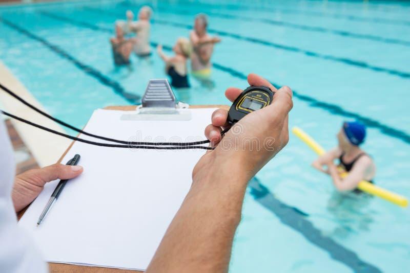 Schwimmentrainer, der Stoppuhr nahe Poolside betrachtet lizenzfreie stockbilder