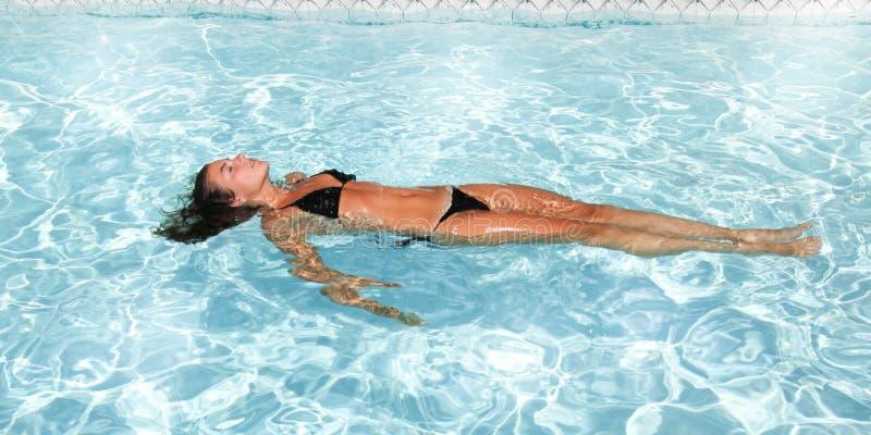 Schwimmenwasser der jungen Frau im Swimmingpool lizenzfreie stockfotos