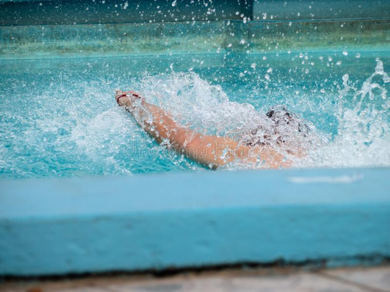 Schwimmerspritzwasser in einem blauen Swimmingpool stockfoto