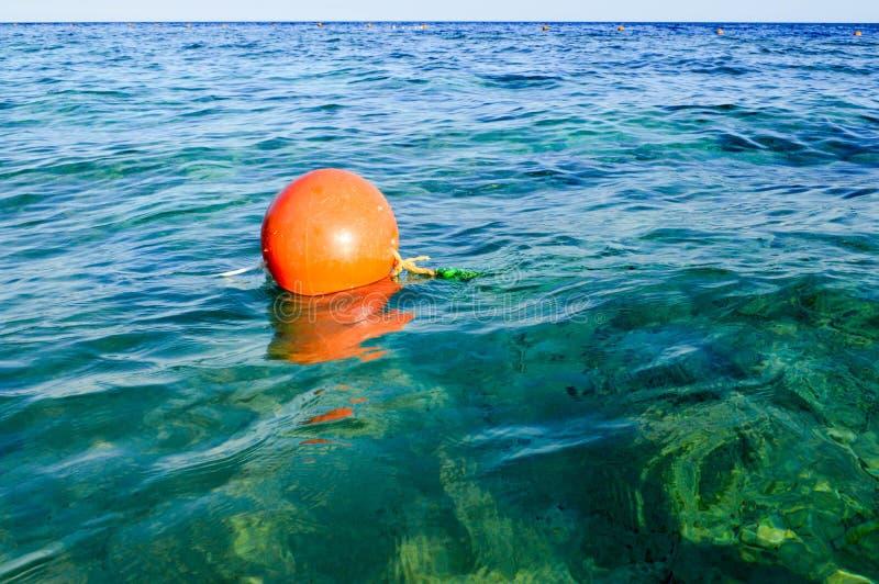 Schwimmt orange großer runder Plastik luft-aufgeblähtes lebensrettendes Leuchtfeuer, Boje in das blaue Salzmeer zur Sicherheit lizenzfreies stockfoto