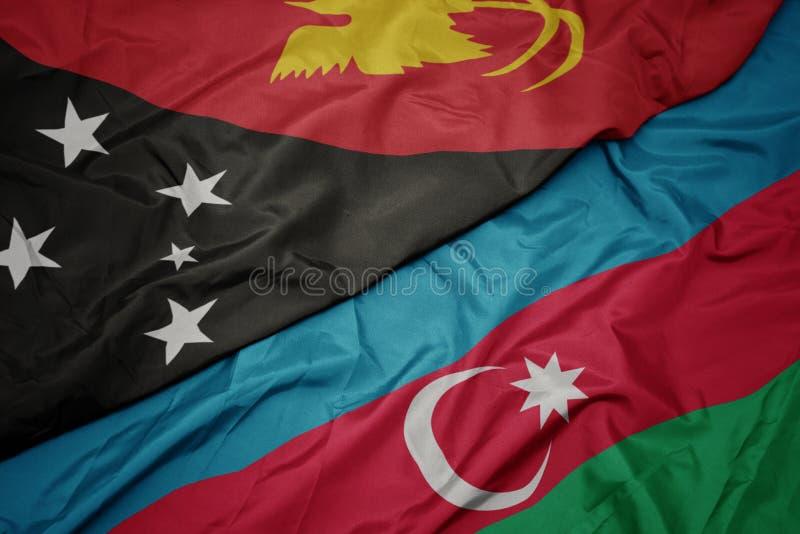 schwindende farbenfrohe Flagge von Azerbaidschan und nationale Flagge Papua-Neuguineas lizenzfreie stockfotos