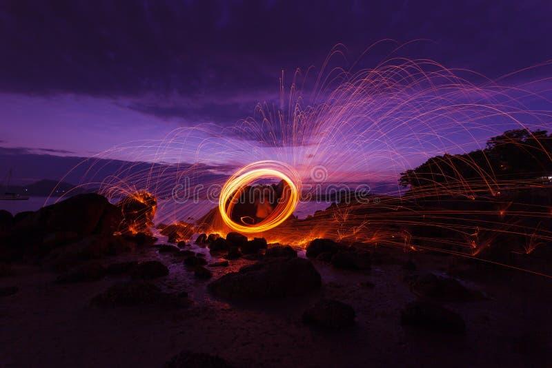Schwingen Sie helle Fotografie der Feuer Strudel-Stahlwolle über dem Stein mit Reflex im schönen Licht des Wassers im Sonnenaufga stockbilder