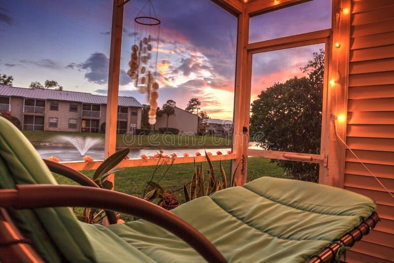 Schwingklubsessel auf einem lanai bei Sonnenuntergang, wie er einen Teich mit einem Brunnen übersieht lizenzfreie stockbilder